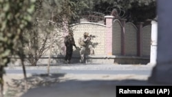 Afghan security personnel take a position near the Shamshad TV station on November 7.