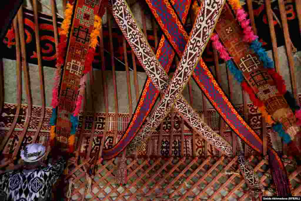 Astara hangs woven fabric to decorate the interior. Past generations used to carry yurts with them to mountain pastures where they would spend the summer tending to herds of livestock.