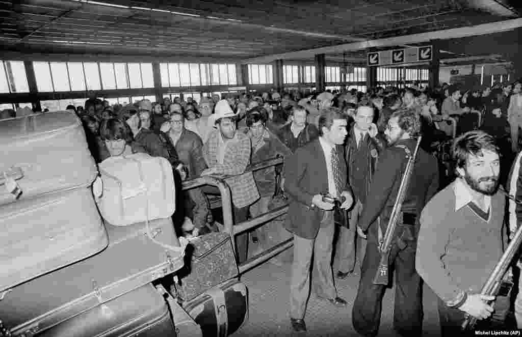 Armed men loyal to Ayatollah Khomeini stand guard at Teheran's Mehrabad International Airport on February 18, 1979. Hundreds of U.S. citizens attempted to board an evacuation flight to leave Iran.