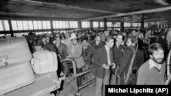ხომეინის შეირაღებული მომხრეები დარაჯობენ მეჰრაბადის საერთაშორისო აეროპორტს თეირანში, 1979 წლის 18 თებერვალს. შტატების ასობით მოქალაქე ირანიდან გარბის.
