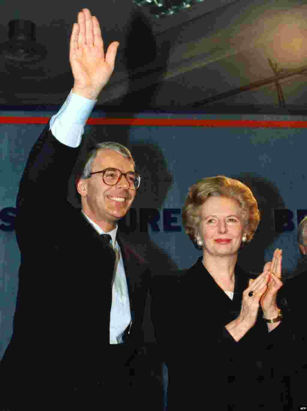 Margaret Thatcher applauds as her successor, John Major, waves in London in March 1992.