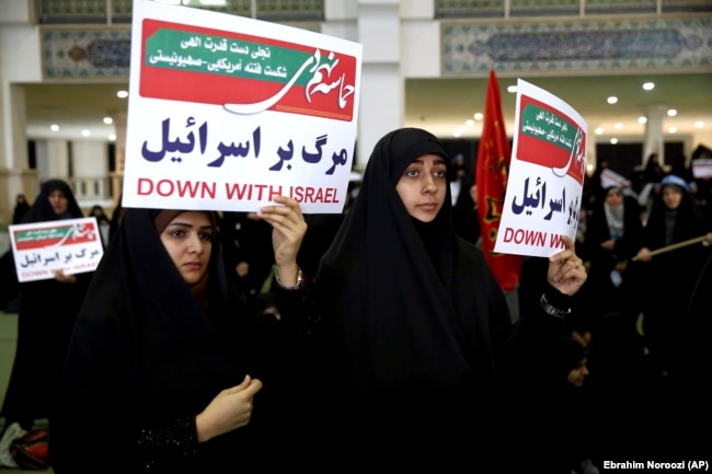 Iranian protesters hold anti-Israeli placards at a rally in Tehran on December 30.