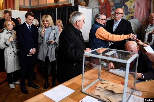 Эммануэль Макрон с супругой (третья слева) голосуют на выборах
