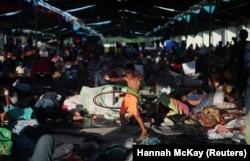 Një migrant, pjesë e karvanit prej mijëra personash që janë nisur nga Amerika Qendrore drejt SHBA-së, luan në një kamp në Juchitan të Meksikës.