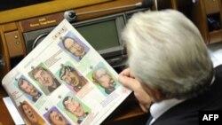 Народний депутат вивчає карикатури своїх колег під час засідання Верховної Ради 21 жовтня 2008 р.