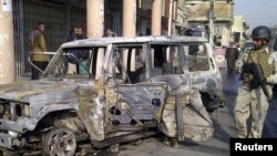 A soldier stands guard near a burnt vehicle after a bomb attack in Alawi district in central Baghdad on December 22.