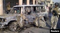 Бағдадтың орталығындағы Алави ауданында полиция жарылған бомбадан өртенген көлікті күзетіп тұр. Ирак, Бағдад, 22 желтоқсан 2011 жыл.