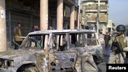 Iraq -- A soldier stands guard near a burnt vehicle after a bomb attack in Alawi district in central Baghdad, 22Dec2011