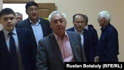 Председатель Союза журналистов Казахстана, президент Национального пресс-клуба Казахстана Сейтказы Матаев (в центре) входит в зал суда. Астана, 23 августа 2016 года.