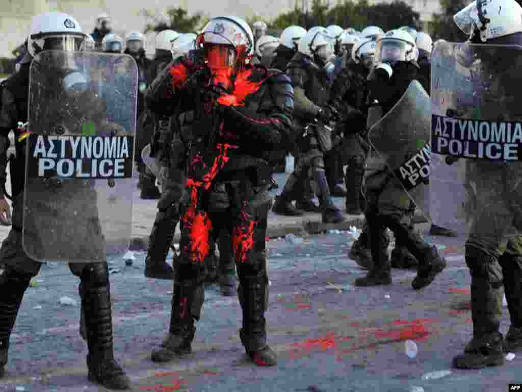 A policeman is hit with red paint while police try to disperse protesters from central Athens' Syntagma Square. (Louisa Gouliamaki for AFP)