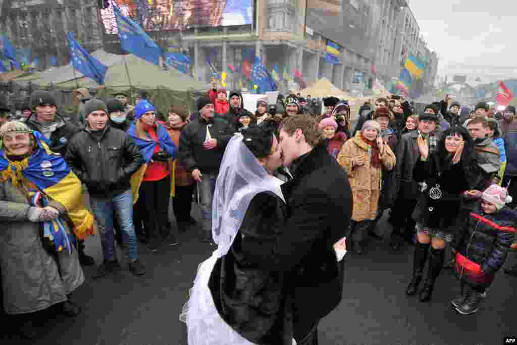 A newly wed couple kiss on Independence Square as pro-European protesters occupy Kyiv's central square, December 21, 2013.