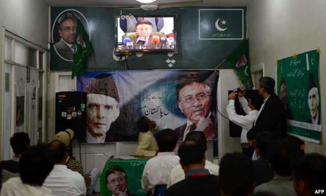 Activists of the All Pakistan Muslim League watch in Karachi as Musharraf speaks to reporters about his return from self-imposed exile on March 1.