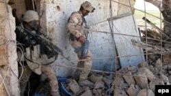 """جنديان عراقيان يتفحصان موقع لمسلحي """"داعش"""" داخل مدينة تكريت"""