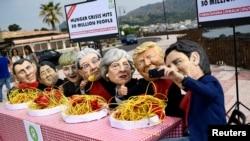 Протестувальники у масках лідерів країн G7 «їдять» лапшу біля місця проведення саміту на Сицилії, Італія, 25 травня 2017 року
