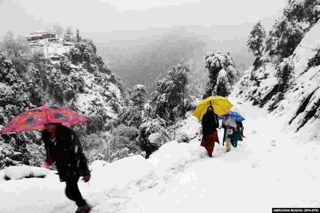People walk during a snowfall in Neelum Valeey in Pakistani-administered Kashmir. (epa-EFE/Amiruddin Mughal)