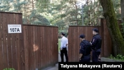 Russian police officers enter a guest-house property used by U.S. diplomats for recreation in Moscow's leafy Serebryany Bor district on July 31.