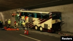 Switzerland -- Emergency services work on the wreckage of a bus that crashed into a motorway tunnel in Sierre, 14Mar2012