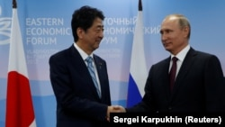 Japanese Prime Minister Shinzo Abe (left) and Russian President Vladimir Putin shake hands during a meeting at the Eastern Economic Forum in Vladivostok, Russia, on September 7.