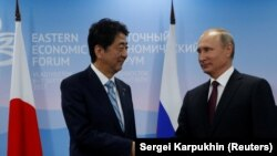 Жапониянын премьер-министри Синдзо Абэ жана Орусиянын президенти Владимир Путин.