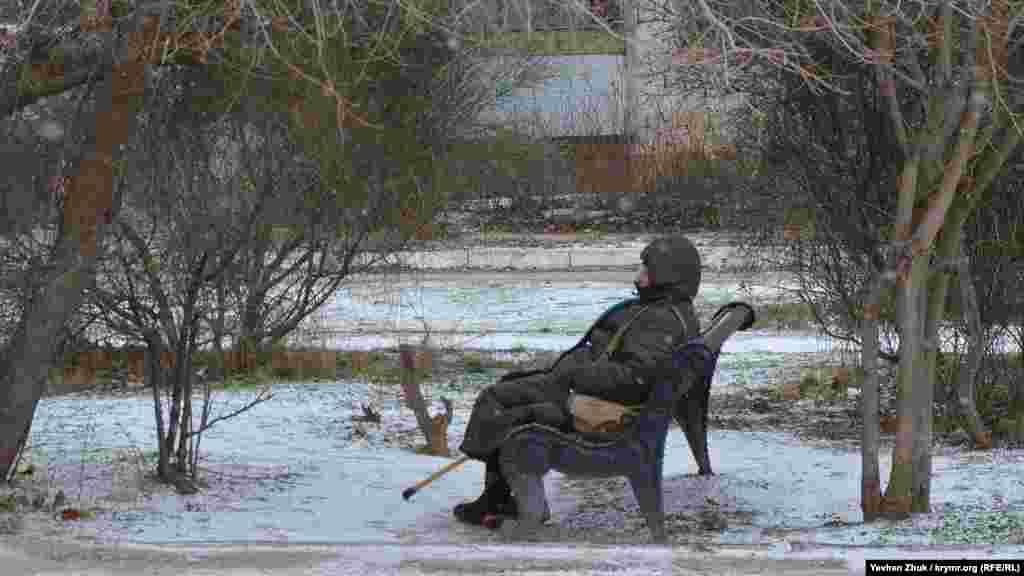 Літня жінка, сидячи на лавці, дихає свіжим морозним повітрям