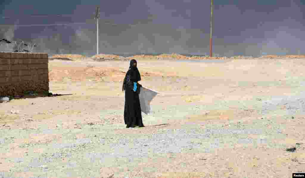 A displaced woman, who fled Islamic State violence, walks on the outskirts of Al Qayyarah, Iraq. (Reuters)