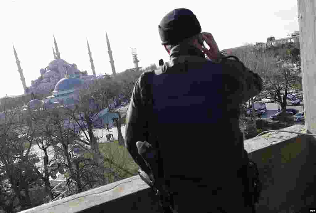 A member of a Turkish SWAT team stands guard on a nearby building.