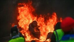 FRANCE -- Demonstrators stand in front of a burning car during a protest of Yellow vests (Gilets jaunes) against rising oil prices and living costs, on December 1, 2018 in Paris