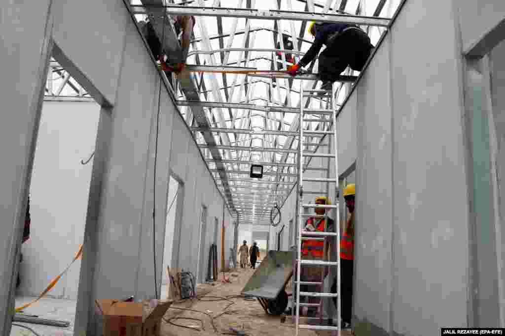 Афганистански работници строят полева болница с капацитет 100 легла в западния град Херат на 29 март. Градът беше определен като епицентър на разпространението на COVID-19 в страната.