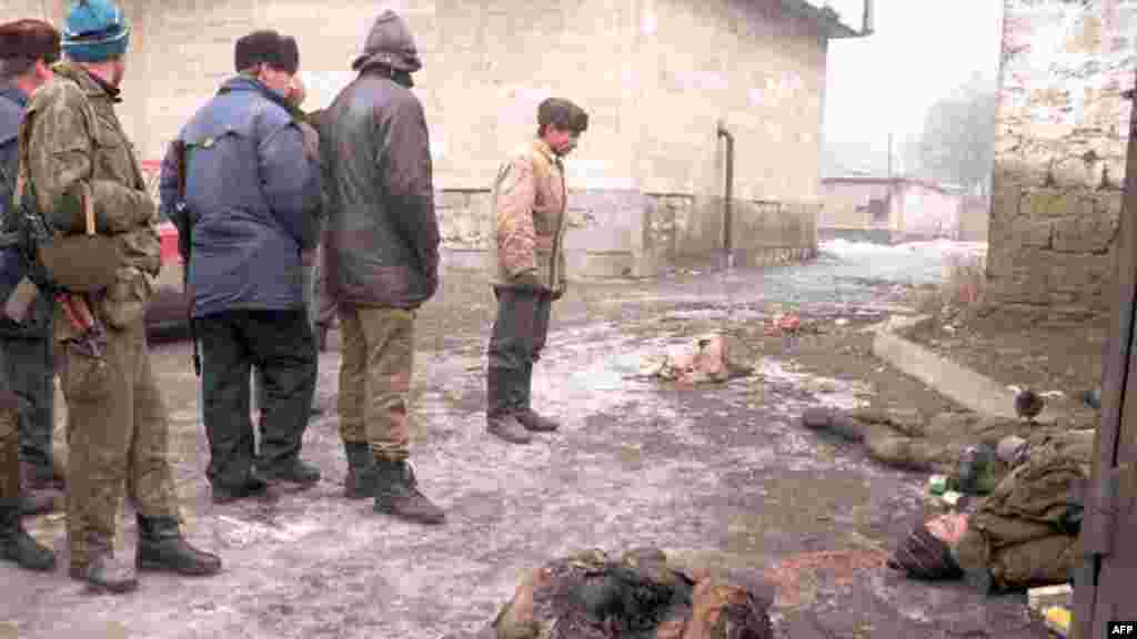 Chechens view the bodies of Russian soldiers on January 1, 1995. After hundreds of Russians died in the initial assault, Russian forces change tactics.