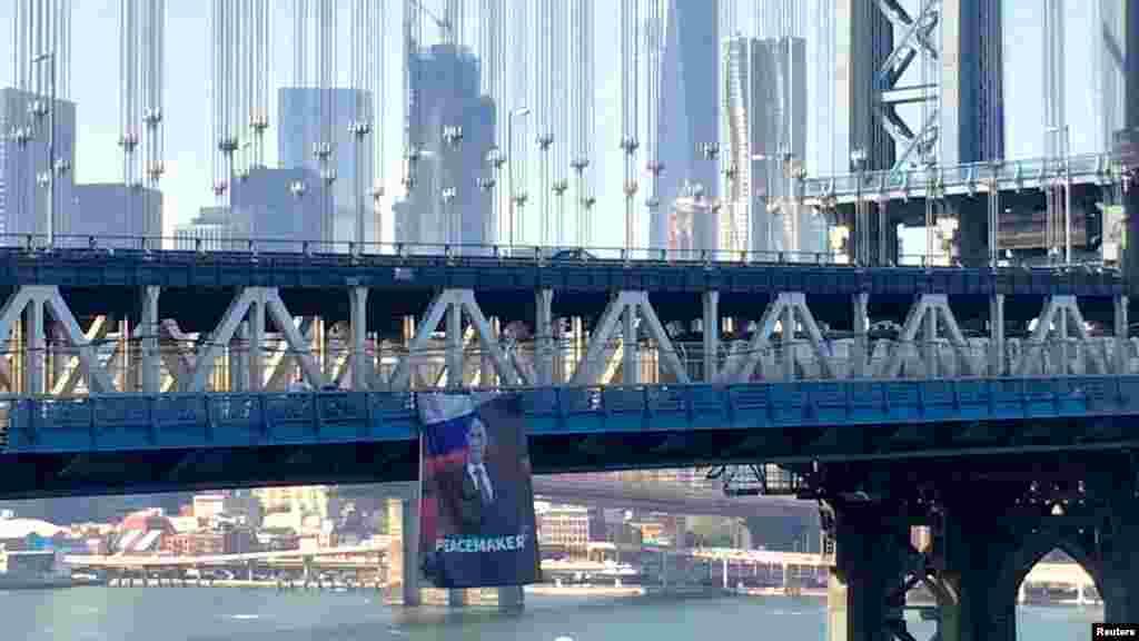 Rus presidenti Wladimir Putiniň rus we Siriýa baýdaklarynyň öňünde çekilen äekili ýerleşdirilen we 7-nji oktýabrda, Putiniň doglan gününde Nýu-Ýork şäherindäki Manhattan köprüsinden asylan plakat. Polisiýa bu plakaty asylan wagtyndan az salym soň aýyrdy we bu hadysany derňeýär. (Reuters/Kathryn Peters)
