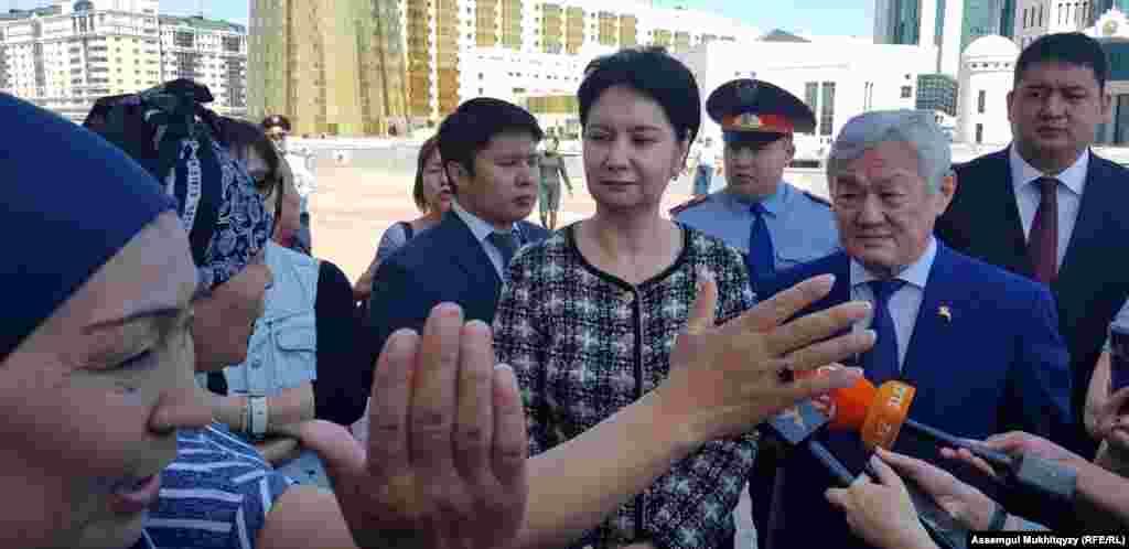К протестующим вышли первый вице-премьер Гульшара Абдыкаликова (вторая справа) и министр труда и социальной защиты населения Бердибек Сапарбаев (первый справа).