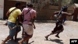 شبهنظامیان وفادار به عبد ربه منصور هادی، در حال خارج کردن یکی از زخمیهای خود از درگیریها در حومه عدن
