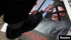 Сүрөттө: түштүк кореялык демонстрант Түндүк Кореянын жол башчысынын сүрөтүн тепсеп жатат, 25-май, 2010-жыл.