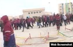 """Люди в рабочей спецовке с надписью """"КазМунайГаз"""" стоят на центральной площади города Жанаозен. 16 декабря 2011 года."""
