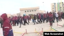 Люди в рабочей спецовке стоят на центральной площади города Жанаозен в день беспорядков 16 декабря 2011 года. Скриншот с видеопортала «Стан.кз».