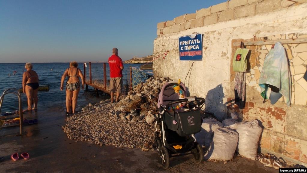 Некоторые отдыхающие купаются в море, несмотря на груды камней.