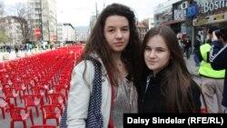 "Lamia Alibegovic, 13, and Elma Ocuz, 14, visit the ""Sarajevo Red Line"" installment."