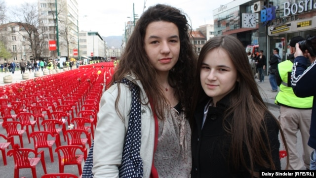 "Lamia Alibegovic, 13, and Elma Ocuz, 14, visit the ""Sarajevo Red Line"" installment."