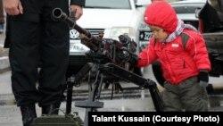 Ребенок рассматривает пулемет, выставленный на показе вооружения. Актау, 13 апреля 2013 года.