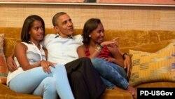 Presidenti Obama dhe dy vajzat e tij, Malia (majtas) dhe Sasha, duke ndjekur në televizion fjalimin e zonjës së parë