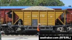 Железнодорожник проходит рядом с грузовым составом на станции в Туркменистане.