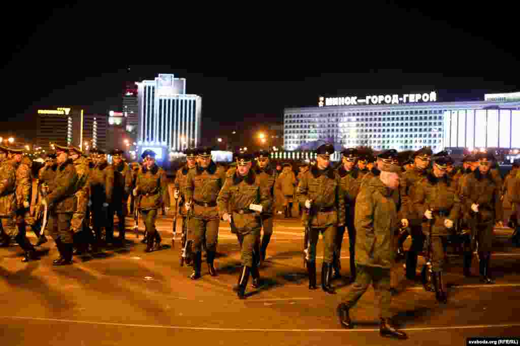 """Soldiers walk across the square with a """"Minsk-Hero-City"""" sign in the background."""