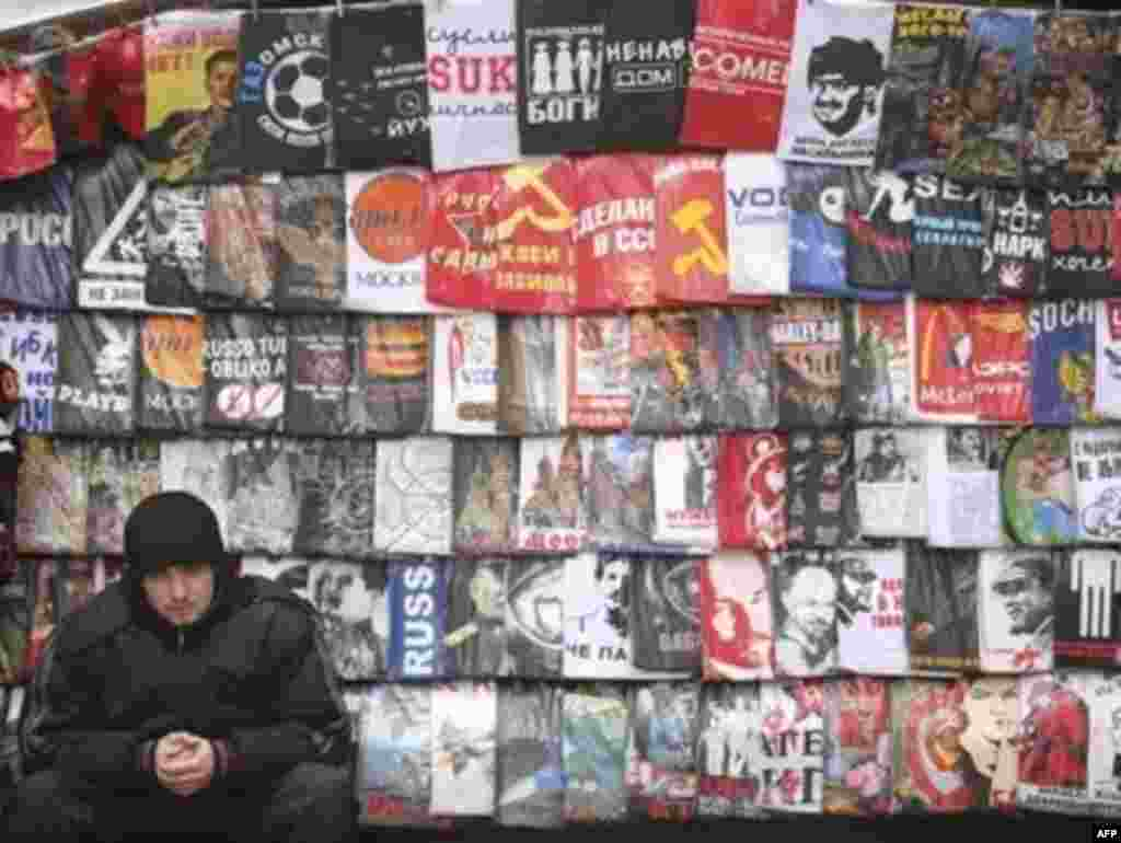 A Moscow vendor flanked by Soviet-themed memorabilia and T-shirts - Both Russians and foreign tourists are in the market for memorabilia glorifying the symbols of the communist past, like these T-shirts on sale at a Moscow street stall.