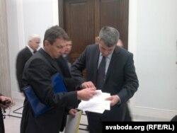 Анджэй Галіцкі і Томаш Пісуля праглядаюць подпісы за вылучэньне Бяляцкага на Нобэля