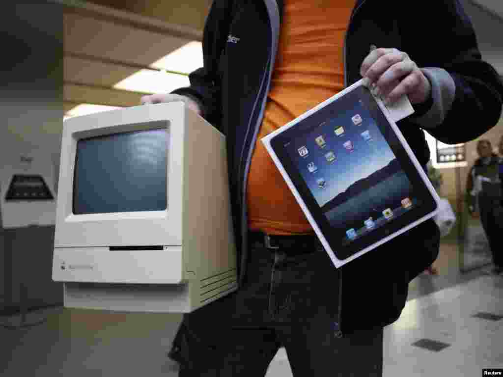 A man shows off his Apple Macintosh Classic computer from 1990 along with his newly purchased Apple iPad at an Apple store in Hamburg, Germany in 2010.