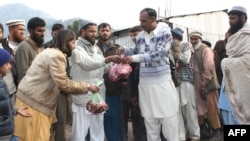Members of Jamaat-ud-Dawa distributing food at a relief camp in Muzaffarabad