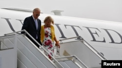 U.S. Vice President Joe Biden (left) and his wife Jill disembark from an aircraft upon their arrival at the airport in New Delhi on July 22.