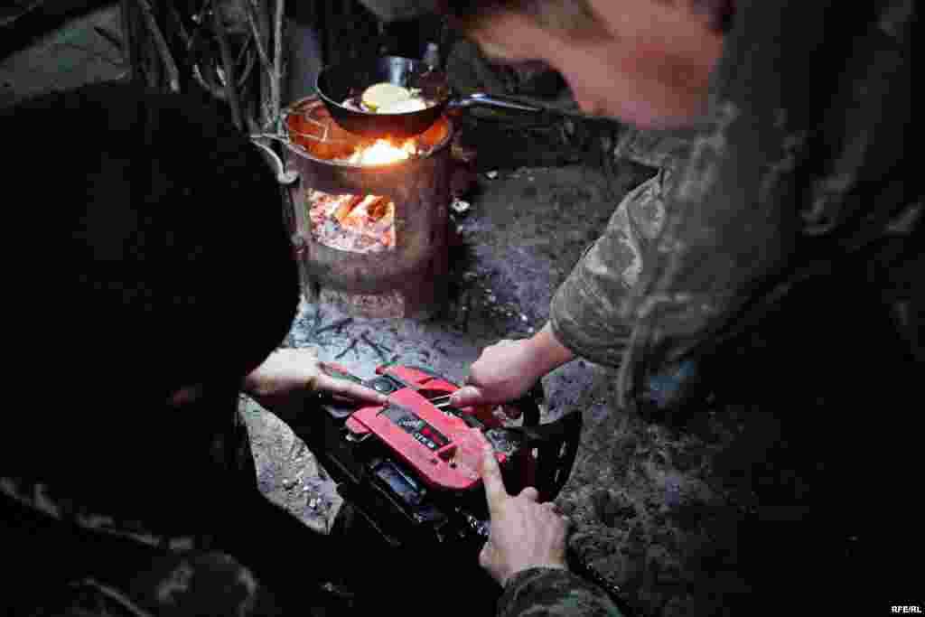 Военные чинят свою бензопилу. Они должны заготовить древесину, чтобы обеспечить передовую дровами для обогрева блиндажей.