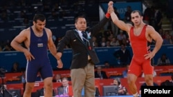 UK -- Armenia's Arsen Julfalakian (R) beats Azerbaijan's Emin Ahmadov on his way to a silver medal in the Men's 74Kg Greco-Roman wrestling during the London 2012 Olympic Games, 05Aug2012.