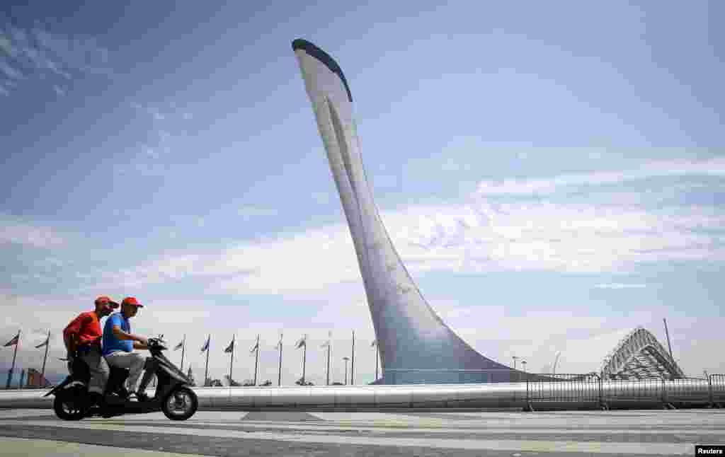 Men ride a scooter through the Olympic park in Sochi, Russia. (Reuters/Maxim Shemetov)
